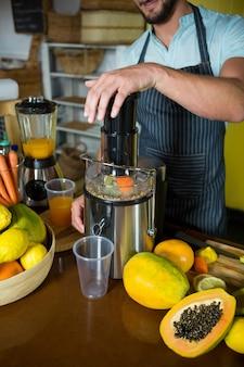 Winkelbediende die papajasap voorbereidt