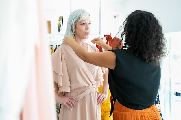 Winkelbediende die vrouwelijke klant helpt om nieuwe jurk te passen. vrouw die kleren in modewinkel kiest. kleding kopen in boetiekconcept