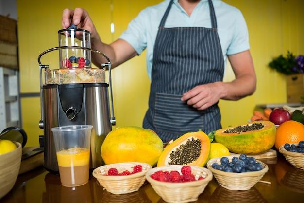 Winkelbediende die vruchtensap voorbereidt