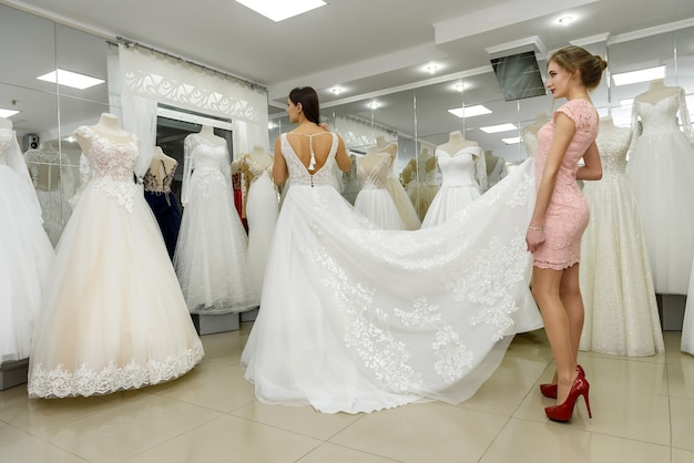 Winkelbediende helpt bruid met trouwjurk in boetiek