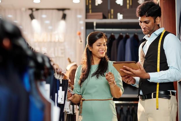 Winkelbediende helpt vrolijke jonge vrouw om broeken te kiezen in warenhuis