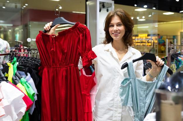 Winkelbediende houdt hanger met rode jurk in de ene hand en blauwe jurk in de andere
