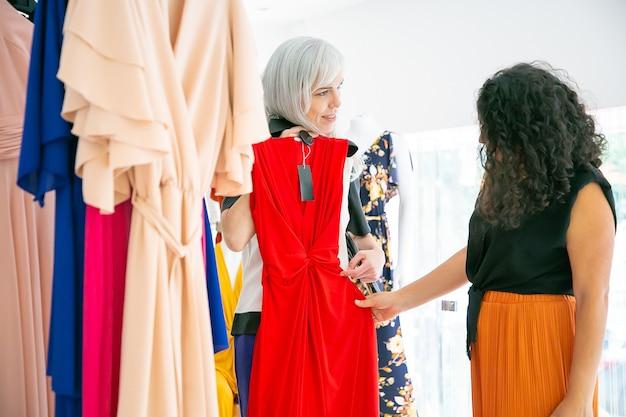 Winkelbediende partij jurk met tag tonen aan klant tussen rekken met kleding. vrouw die avondkleding kiest. zijaanzicht. modewinkel of winkelconcept