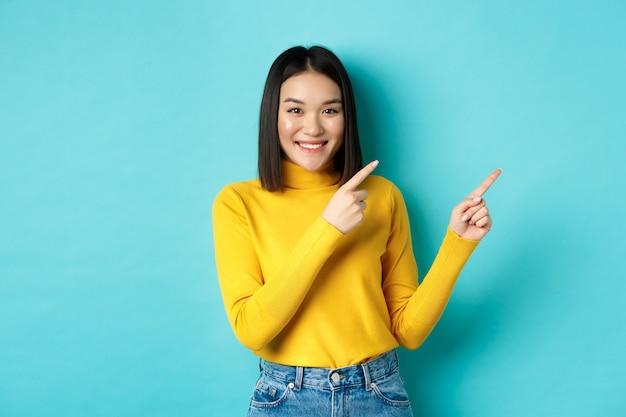 Winkelconcept. aantrekkelijk aziatisch meisje in trendy trui die reclame toont, met de vingers naar rechts wijst en glimlacht, promotiedeal aanbeveelt, blauwe achtergrond