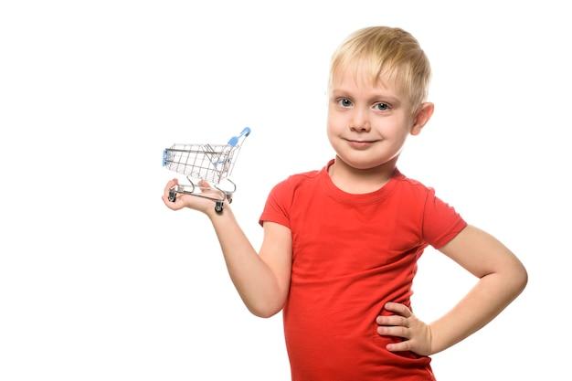 Winkelconcept. blonde schattige kleine lachende jongen in rood t-shirt met een klein metalen winkelwagentje. isoleer op witte achtergrond.