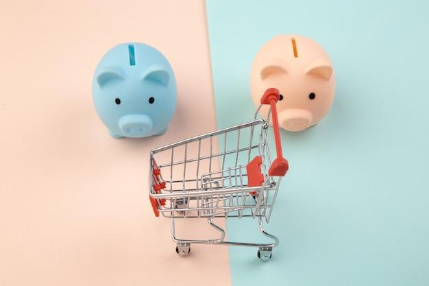 Winkelconcept, economie, besparingen. spaarvarken twee met supermarktkarretje op kleurrijke achtergrond