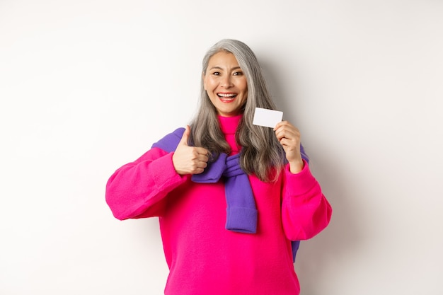 Winkelconcept. glimlachende aziatische vrouw van middelbare leeftijd met grijs haar die plastic creditcard en duim-omhoog toont, die bankbevordering, witte achtergrond aanbeveelt.