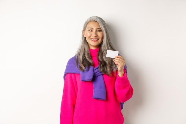 Winkelconcept. glimlachende aziatische vrouw van middelbare leeftijd met grijs haar die plastic creditcard toont en gelukkig kijkt, die zich over witte achtergrond bevindt.