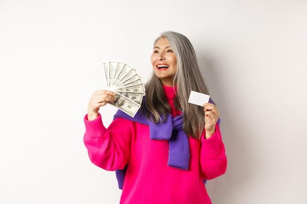 Winkelconcept. stijlvolle aziatische senior vrouw die gelddollars en plastic creditcard toont, dromerig opzij kijkt, overweegt te kopen, witte achtergrond.