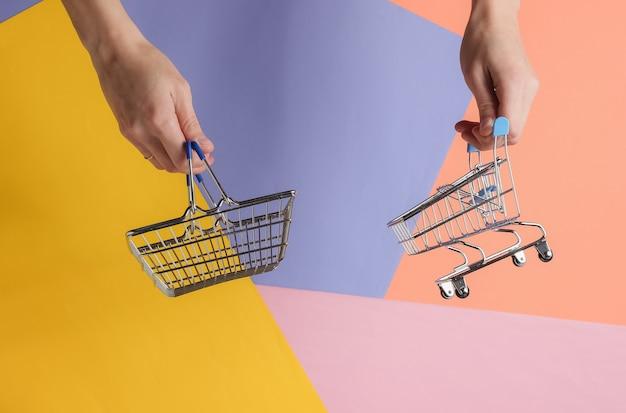 Winkelconcept vrouwelijke hand houdt mini winkelmandje en trolley op gekleurde achtergrond