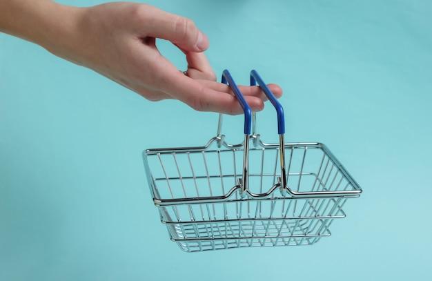 Winkelconcept vrouwelijke hand houdt mini winkelmandje