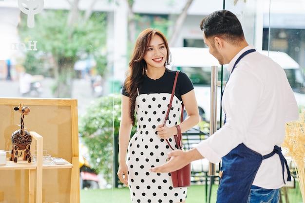 Winkeleigenaar die deur voor klant houdt