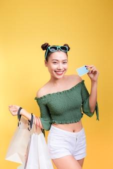 Winkelen aziatische vrouw houdt boodschappentassen en een creditcard op gele achtergrond