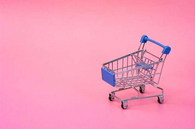 Winkelen concept: blauw winkelwagentje op roze. online winkelen consumenten kunnen winkelen vanuit huis en bezorgservice. met kopie ruimte