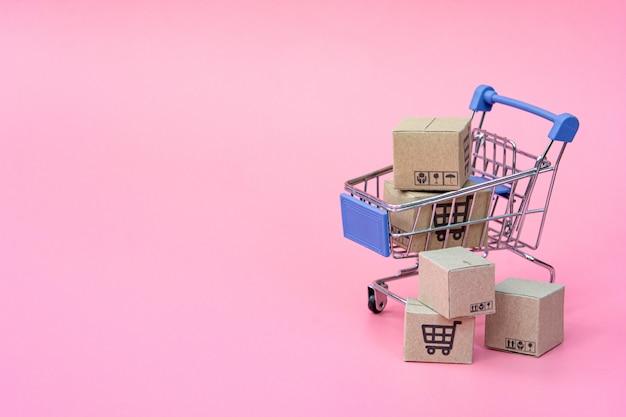 Winkelen concept: dozen of kartonnen dozen in blauwe winkelwagen op roze achtergrond. online winkelen consumenten kunnen winkelen vanuit huis en bezorgservice. met kopie ruimte