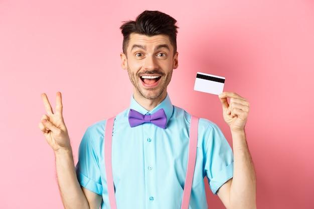 Winkelen concept. glimlachende kaukasische kerel in vlinderdas die plastic creditcard en vrede, overwinningsteken toont, die zich gelukkig op roze achtergrond bevinden.