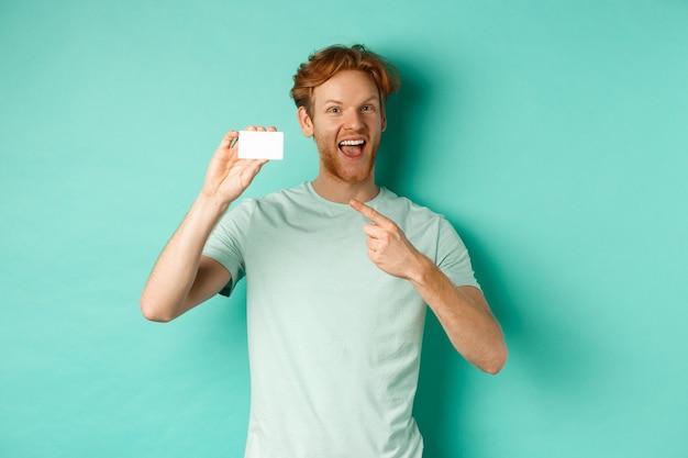 Winkelen concept. knappe roodharige man in t-shirt met plastic creditcard en glimlachen, staande op turkooizen achtergrond.