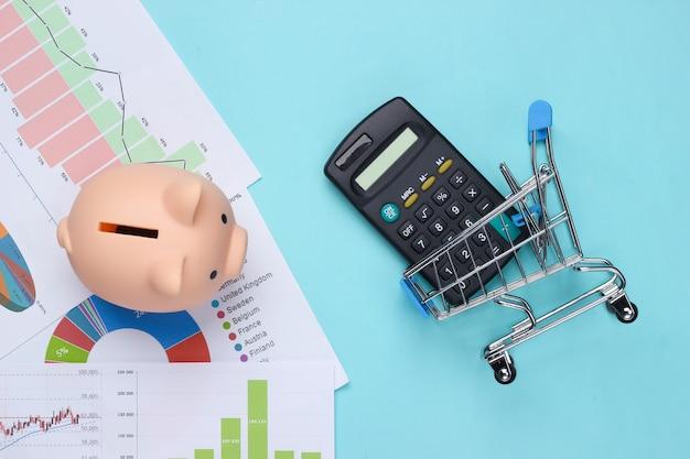 Winkelen concept. spaarvarken met grafieken en diagrammen, supermarktkarretje, rekenmachine op een blauw