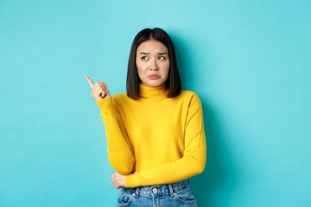 Winkelen concept. teleurgestelde en sombere aziatische vrouw mokkend boos, wijzende vinger links naar slecht nieuws banner, staande op blauwe achtergrond.