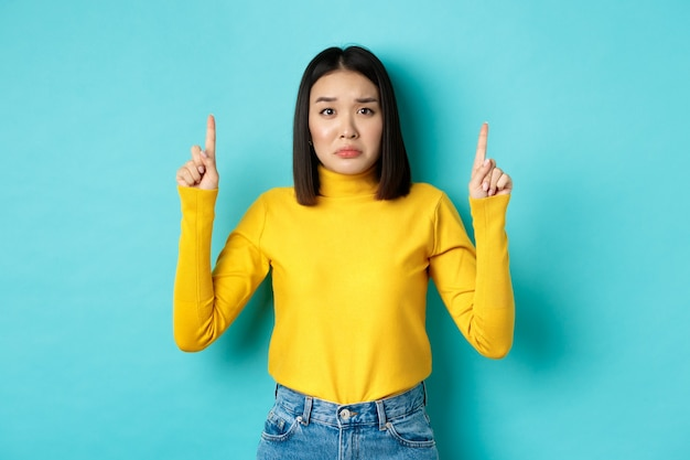 Winkelen concept. teleurgestelde en sombere aziatische vrouw mokkend boos, wijzende vingers omhoog naar slecht nieuws banner, staande op blauwe achtergrond.