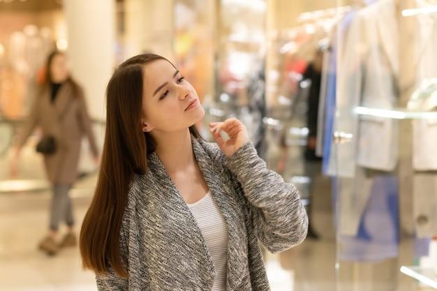 Winkelen een jong meisje kijkt naar etalages, kiest cadeaus in een winkelcentrum.