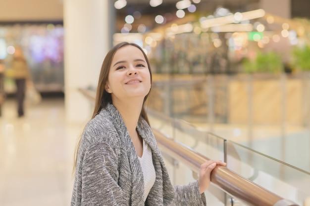 Winkelen een jong meisje kijkt naar etalages, lacht, doet aankopen in een winkelcentrum.