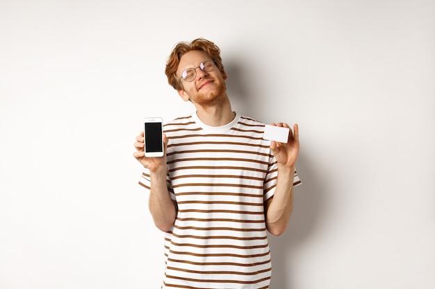 Winkelen en financiën concept. blij jonge man met rood haar glimlachend van tevredenheid, smartphone leeg scherm en creditcard, witte achtergrond tonen.