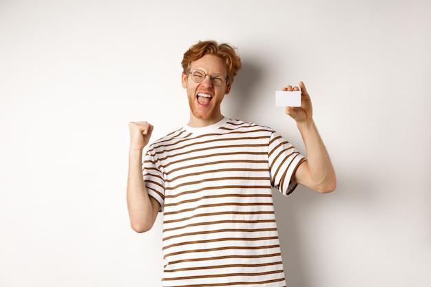 Winkelen en financiën concept. jonge man die bankprijs wint, plastic creditcard toont en vuistpomp maakt, schreeuwend van vreugde en tevredenheid, witte achtergrond
