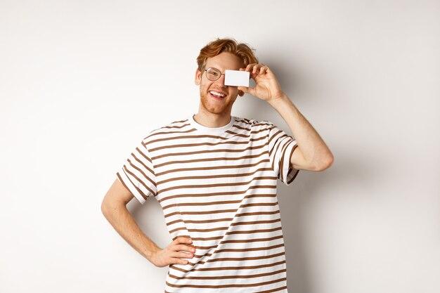 Winkelen en financieren concept. gelukkig jonge man met rood haar en bril met plastic creditcard in de buurt van gezicht, glimlachend vreugdevol op camera, staande op witte achtergrond.