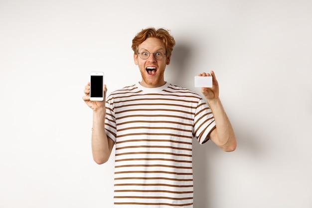 Winkelen en financieren concept. jonge man met leeg mobiel scherm en plastic creditcard, glimlachend in de camera, witte achtergrond.