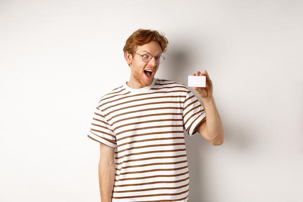 Winkelen en financieren concept. opgewonden jonge man met rood haar, starend naar plastic kaart en schreeuw van vreugde, staande op een witte achtergrond.
