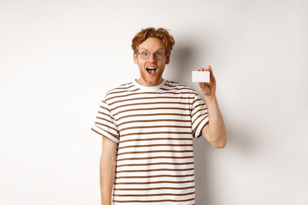 Winkelen en financieren concept. verbaasde jonge man met baard en rood haar met plastic creditcard en op zoek onder de indruk, witte achtergrond.