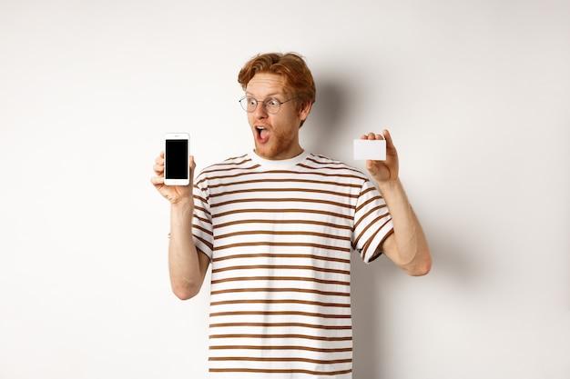 Winkelen en financieren concept. verbaasde jongeman met rood haar met plastic creditcard en leeg scherm van smartphone, starend naar vertoning onder de indruk, witte achtergrond.