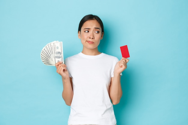 Winkelen, geld en financiën concept. besluiteloos en verward aantrekkelijk aziatisch meisje kan niet beslissen wat beter is, creditcard of contant geld, kijkt perplex, staat nadenkend over blauwe muur