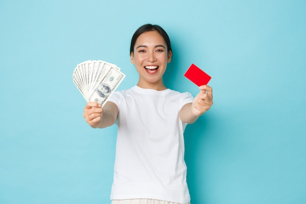Winkelen, geld en financiën concept. gelukkig en tevreden glimlachend aziatisch meisje dat dollars in contanten en creditcard met trotse uitdrukking toont, die zich tevreden over lichtblauwe muur bevindt.