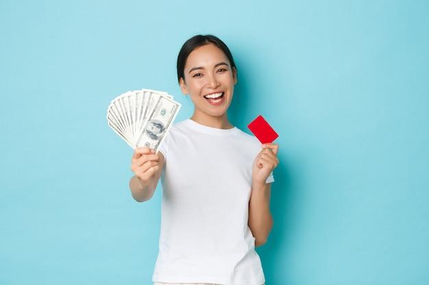 Winkelen, geld en financiën concept. gelukkig zorgeloos aziatisch meisje in wit t-shirt met creditcard maar in plaats daarvan contant geld te kiezen. houd niet van contactloos betalen, vrolijk lachend, blauwe muur