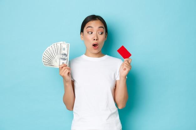 Winkelen, geld en financiën concept. verbaasd mooi aziatisch meisje in wit t-shirt hijgend verbaasd en kijkend naar creditcard terwijl ze contant geld in de andere hand houdt, geeft de voorkeur aan contactloze betaling.