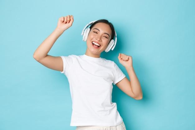 Winkelen, geld en financiën concept. vrolijk aziatisch meisje in wit casual t-shirt, karaoke zingen, muziek-app afspelen, muziek luisteren in draadloze oortelefoons en genieten van perfect geluid.