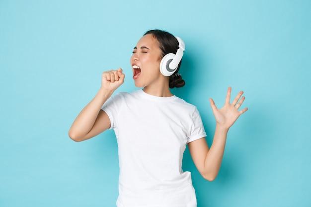 Winkelen, geld en financiën concept. vrolijk aziatisch meisje in wit casual t-shirt, karaoke zingen, muziek-app spelen, muziek luisteren in draadloze oortelefoons en genieten van perfect geluid