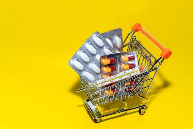 Winkelen geneeskunde concept. diverse capsules, tabletten en medicijnen en een thermometer in winkelkar op. creatief idee voor gezondheidszorg en farmaceutisch bedrijf.