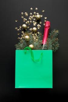 Winkelen groene papieren zak met kerstcadeaus, mousserende wijn, rode kerstballen en glanzende gouden sneeuwvlokken op zwarte ruimte
