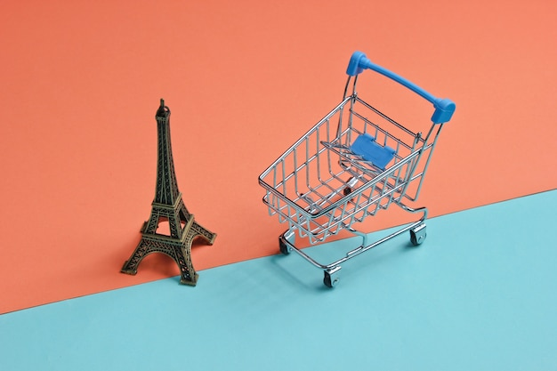 Winkelen in het minimalistische concept van parijs. winkelwagen, eiffeltoren beeldje op koraal blauwe achtergrond.