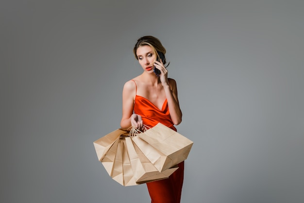 Winkelen lachende vrouw met tas en mobiele telefoon