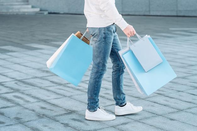 Winkelen man casual stedelijke consumentisme benen in spijkerbroek papieren zakken in handen