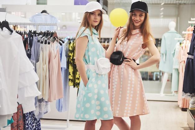 Winkelen met bestie. achtermening van twee mooie vrouwen die met het winkelen zakken camera met glimlach bekijken terwijl het lopen bij de kledingsopslag