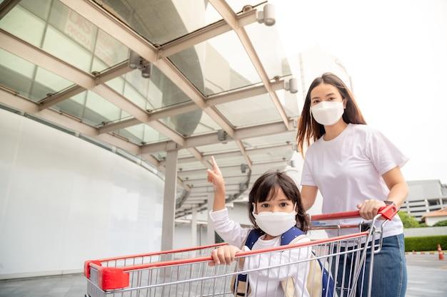 Winkelen met kinderen tijdens een virusuitbraak. aziatische moeder en dochter die chirurgisch gezichtsmasker dragen die naar de supermarkt gaan.