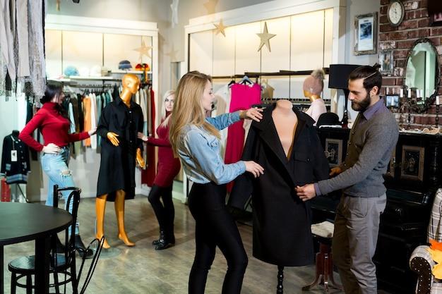 Winkelen, mode, kleding, stijl en mensen concept - gelukkige vrienden proberen jas in winkelcentrum of kledingwinkel