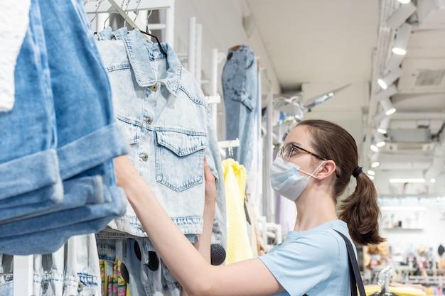 Winkelen, mode, stijl en mensen tijdens covid19 - een mooi jong meisje met een medisch masker om zichzelf te beschermen tegen coronavirus kiest kleding in een winkel. nieuw normaal concept.