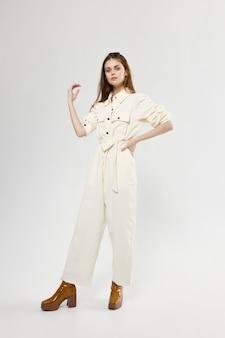 Winkelen modieuze vrouw in een witte laars jumpsuit op een lichte achtergrond gebaren met haar handen. hoge kwaliteit foto