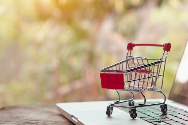 Winkelen online concept. leeg winkelwagentje of trolley op laptop toetsenbord. boodschappenservice op het online web. biedt levering aan huis.